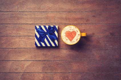 Tasse Cappuccino mit Herz Milchschaum und einem Weihnachtsgeschenk